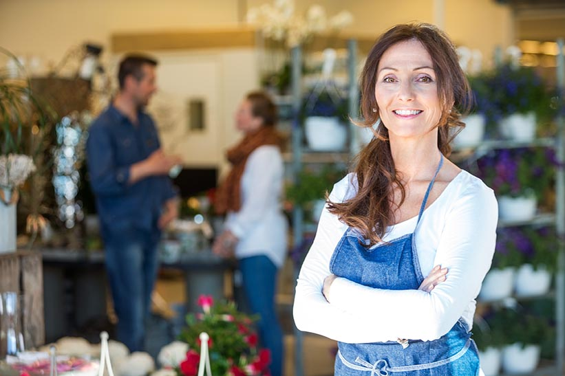 Portrait of smiling mid adult florist with customers in background at flower shop